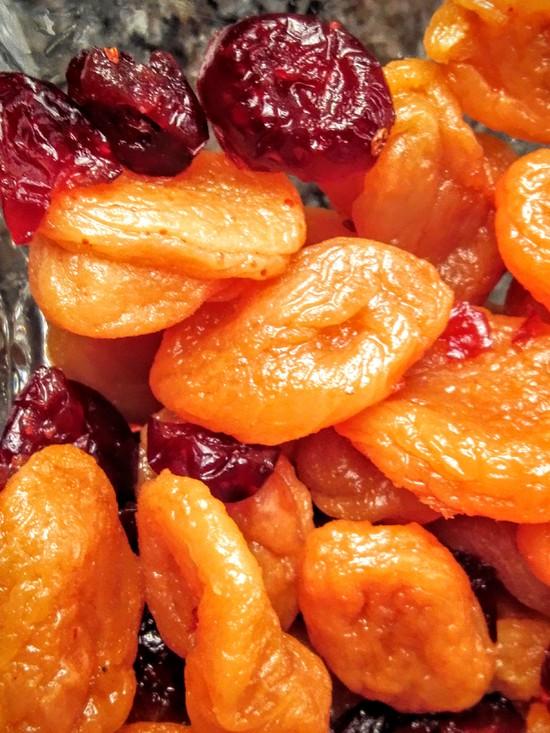 Nach der Einweichzeit die Aprikosen und Cranberries über dem Sieb gut abtropfen lassen, damit der Far nicht klitschig wird. Tipp: Den Saft auffangen und beispielsweise für eine Quarkspeise verwenden. Außerdem den Backofen auf 180 Grad Ober-, Unterhitze vorheizen sowie die Milch und die Sahne in den Messbecher geben.