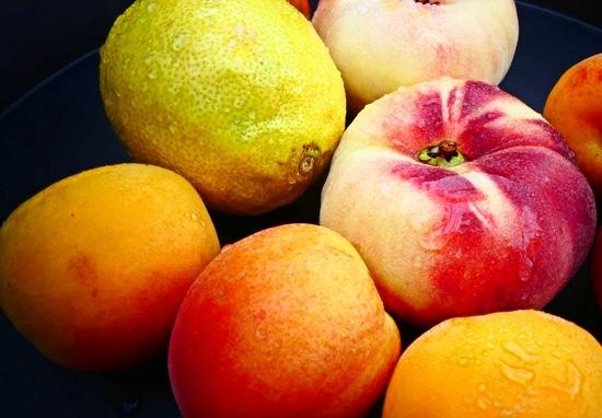 Drei Aprikosen und einen Plattpfirsich waschen, halbieren und entkernen. Tipp: Je nach Leistungsstärke des Standmixers oder Pürierstabs kann es sinnvoll sein, die Früchte in kleinere Stücke zu schneiden.