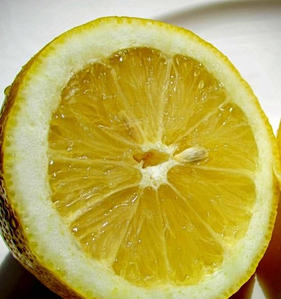 Eine Zitrone halbieren und zunächst nur eine Hälfte auspressen.