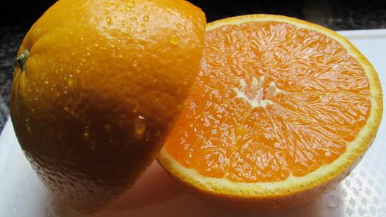 In der zweiten kleinen Rührschüssel die Glasur zubereiten. Dafür eine Orange zunächst halbieren und eine Hälfte auspressen.