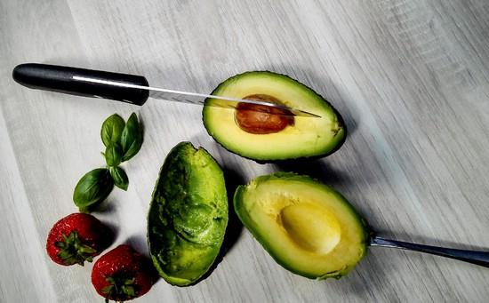 Dann die Avocado halbieren, den Kern rausnehmen und das Fruchtfleisch auslöffeln.