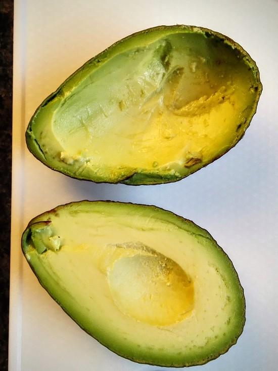 Daran anschließend die Avocado waschen, trocknen mit dem Küchentuch, halbieren, den Kern entfernen, die Hälften etwas aushöhlen und die Avocadohälften in die Auflaufform geben.