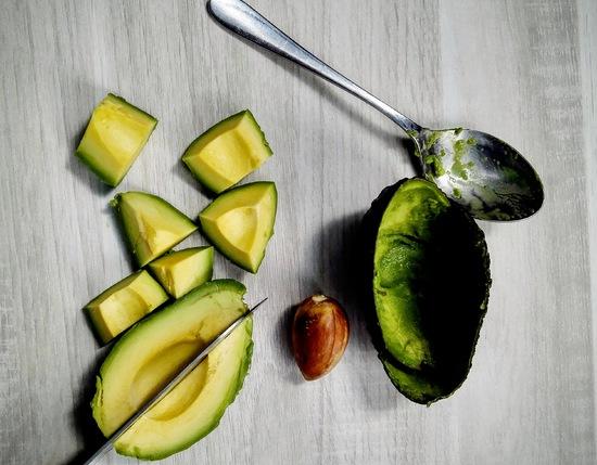 Nun die Avocado in Stücke schneiden und diese ebenso in den Standmixer geben.