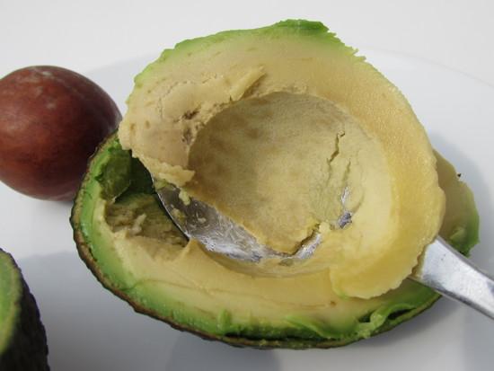Nun die Avocado halbieren, den Kern rausnehmen, das Fruchtfleisch aus einer der Hälften auslöffeln und zum Kefir in den Standmixer geben.