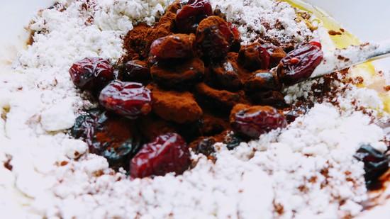 Das Mehl, das Backpulver, die Prise Salz, den Backkakao, den Kokosblütenzucker und die Cranberries hinzufügen. Tipp: Man kann die trockenen Zutaten auch erst in einer mikrowellengeeigneten Müslischale miteinander verrühren und dann die flüssigen Zutaten hinzufügen.