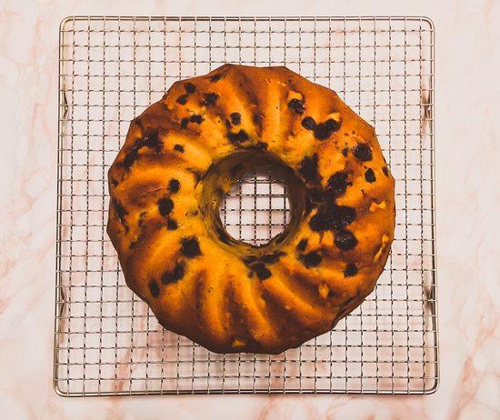 Den Kuchen aus dem Backofen holen, kurz auskühlen lassen und dann auf das Kuchengitter geben.