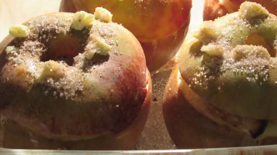 Nach 15 Minuten die Auflaufform aus dem Ofen holen und die Deckel auf die Äpfel legen und Butterflocken auf die Deckel geben sowie die restliche Zimt-Zucker-Mischung auf die Deckel streuen.