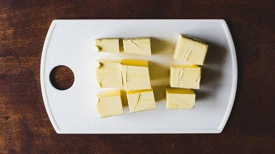 Vorbereitend die Butter in Stücke schneiden.