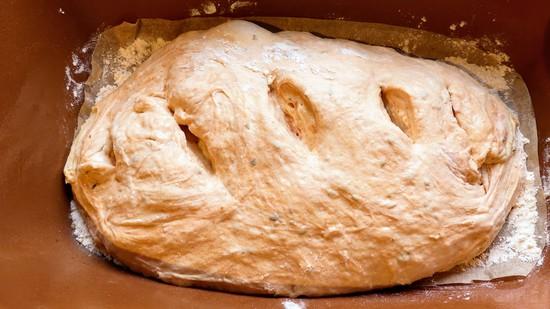 Den vorgeformten Brotlaib in den vorbereiteten Römertopf geben, eventuell nachformen und mit der Schere den Teig einschneiden. Tipp: Ich verwende hier eine Küchenschere, weil man damit diesen klebrigen Teig am besten einschneiden kann.