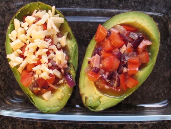 Abschließend etwas geriebenen Käse auf die Avocadohälften geben und die Auflaufform für 15 bis 20 Minuten in den vorgeheizten Ofen geben.