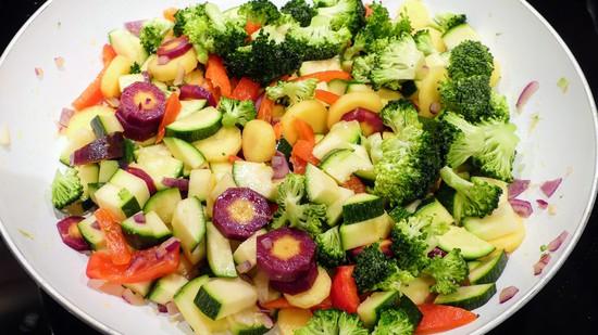 Gleichzeitig die Knoblauchscheiben mit den Zwiebelwürfeln und dem vorbereiteten Gemüse in die zweite Pfanne geben, mit Harissa, Salz, Pfeffer sowie Kurkuma würzen und anschmoren.