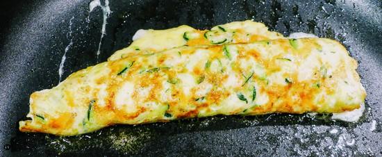 Die Eirolle noch ein klein wenig in der Pfanne braten, so dass der Mozzarella im innern der Eirolle schmelzen kann.