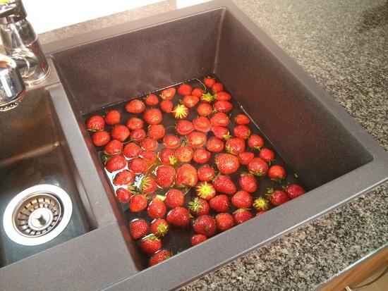 Zunächst werden die Erdbeeren gewaschen, aber man sollte sie nicht zu lange im Wasser liegen lassen. Dann lässt man sie im Sieb gut abtropfen oder trocknet sie vorsichtig.