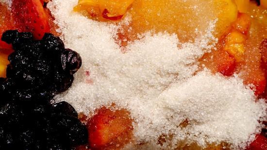 Dann die Aroniabeeren hinzufügen, alle Früchte mit dem Gelierzucker bedecken und die Mischung mindestens 3 Stunden ziehen lassen.