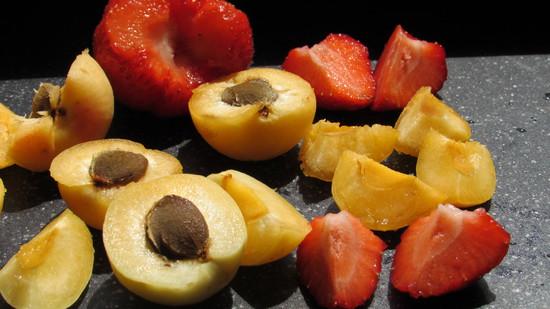 Die Aprikosen halbieren, entsteinen und vierteln, die Erdbeeren entkelchen und vierteln.