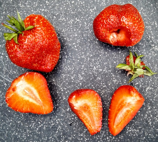Ebenso die Erdbeeren trocknen, dann entkelchen, vierteln und zu den Nektarinen geben.