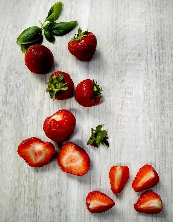 Jetzt die Erdbeeren waschen, entkelchen, vierteln und zu den anderen Zutaten im Standmixer hinzufügen. Tipp: Entkelchen bedeutet, dass der Blütenansatz der Erdbeere (also die grünen Kelchblätter) entfernt werden.