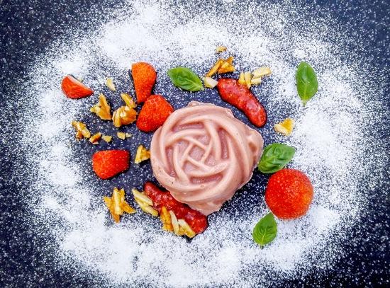Abschließend noch mit Mandelkrokant, Erdbeerpüree, einzelnen Erdbeeren und Basilikumblättern sowie Puderzucker garnieren und servieren.