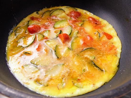 Nun erneut einen Esslöffel Olivenöl in der Pfanne erhitzen, die Ei-Gemüsemasse in die Pfanne gießen und alles bei mittlerer Hitze stocken lassen.
