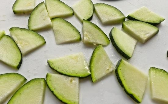 Das Zucchinistück der Länge nach halbieren. Die Hälften danach nochmals halbieren, in Scheiben schneiden und diese zu dem Knoblauch in die Pfanne geben.