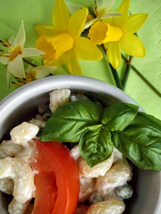 Nun für die Garnitur die Tomate waschen, entstielen, vierteln und den Nudelsalat damit garnieren. Wer mag, garniert den Salat auch mit Kräutern, wie beispielsweise Basilikum.