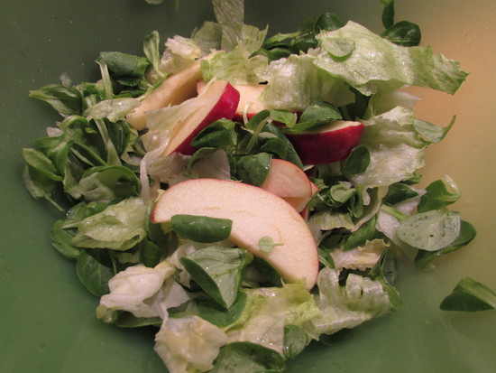 Zum Schluss den Apfel waschen, vierteln, das Kerngehäuse enfernen, die Viertel in Spalten schneiden und diese zum Salat geben.