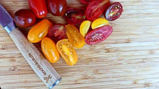 Die kleinen Tomaten waschen, halbieren und auch erst einmal an die Seite stellen. Tipp: Bei größeren Tomaten immer das Grüne vom Stiel und die Kerne entfernen. Bei den kleinen Tomaten ist dies jedoch nicht nötig.