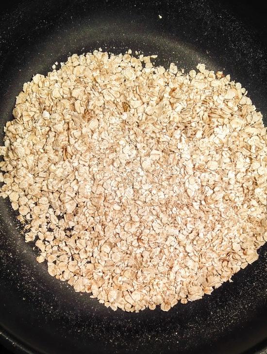 Die Haferflocken in eine Pfanne geben, ohne Fett anrösten, auf einen Teller geben und beiseite stellen.