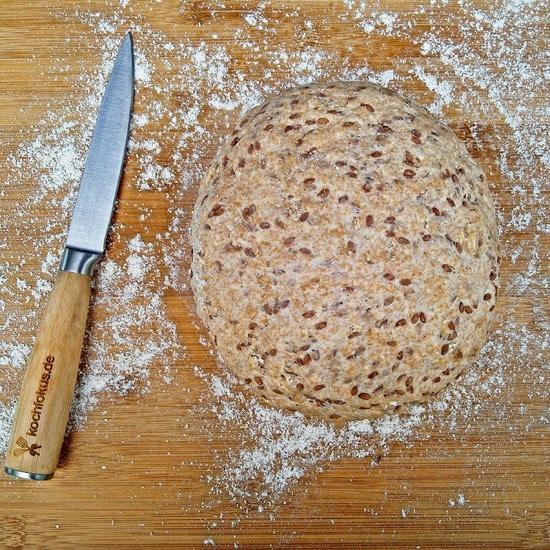 Wenn das Volumen des Teiges sich verdoppelt hat, wird er auf der bemehlten Arbeitsfläche nochmals durchgeknetet und zu einem runden Brot geformt.