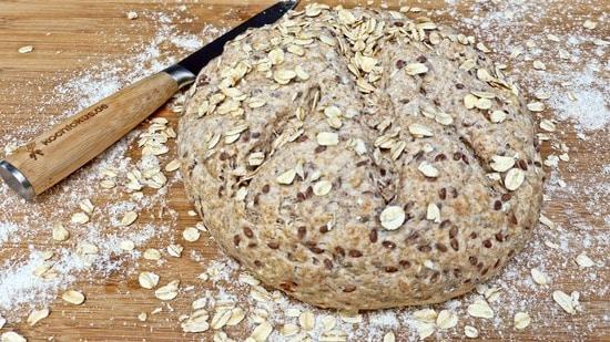 Die Haferflocken auf dem Brotlaib verteilen, diesen dann mit einem scharfen Messer einschneiden und nochmals mit dem Küchentuch abdecken.