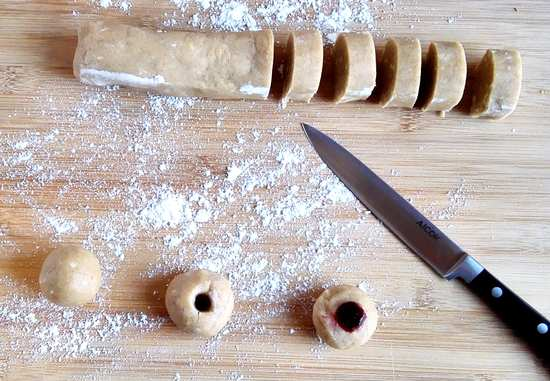 Mit einem Messer möglichst gleich große Scheiben von der Rolle abschneiden. Diese zu kleinen Kugeln formen und auf das mit Backpapier ausgelegte Backblech setzen. Tipp: Darauf achten, dass etwa 2 cm Abstand zwischen den Kugeln ist.