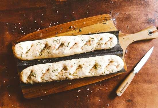 Nach den 10 Minuten die Baguettes mit einem scharfen Küchenmesser einige Male schräg einschneiden, mit Wasser besprühen und das Himalaya Steinsalz sowie den Rosmarin als Topping darüber streuen.