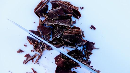 Für die Glasur nun die Kuvertüre mit einem Messer zerkleinern und die Hälfte der zerkleinerten Kuvertüre in die Wasserbad-Schmelzschale oder in die Metallschüssel geben.