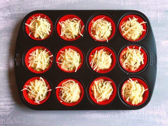 Auf jeden Muffin noch nach Belieben geriebenen Käse geben.
