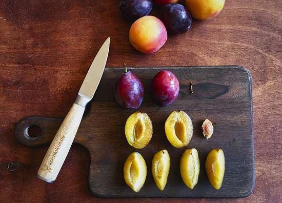 Die Pflaumen waschen, etwas abtrocknen, halbieren, den Stein jeweils entfernen und die Früchte vierteln. Die Viertel zunächst in die Schüssel für das Obst geben.