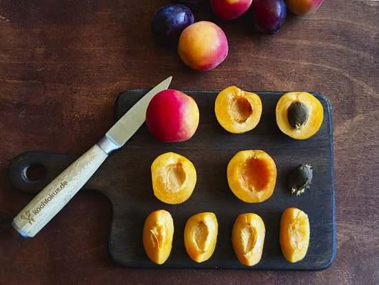 Ebenso die Aprikosen  waschen, etwas trocknen, halbieren, den Kern entfernen und die Früchte in Viertel schneiden. Auch diese erst einmal zu den Pflaumenvierteln geben.