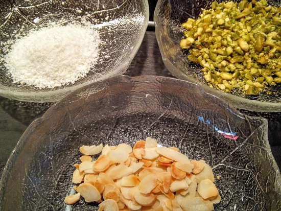 Außerdem die Koksraspeln und die Mandeln jeweils auf einen Teller geben.