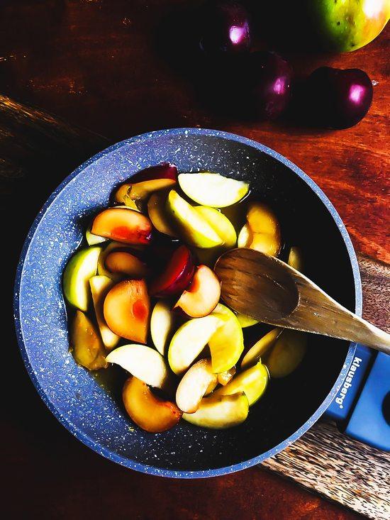 Den Apfel ebenso waschen, abtrocknen, das Kerngehäuse entfernen, in Spalten schneiden und auch in die Pfanne geben.