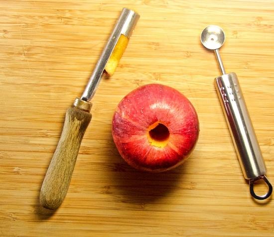 Danach den Apfel waschen, das Kerngehäuse ausstechen, den Deckel abschneiden und mit dem kleinen Kugelausstecher vorsichtig etwas aushöhlen. Außerdem den Apfel in die vorbereitete Auflaufform geben. Den Deckel zunächst beiseite legen.