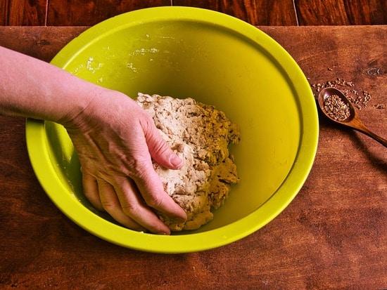 Dann die Leinsamen dazu geben und von Hand einarbeiten.Dabei den Teig in der Schüssel schön kneten.