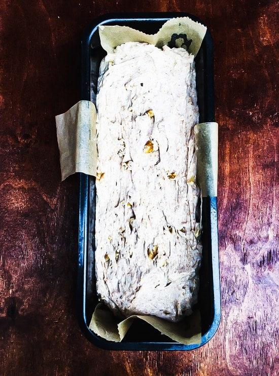 Den Teig direkt aus der Schüssel in die vorbereitete Backform geben. Tipp: Der Teig ist sehr klebrig. Du kannst ihn entweder ganz einfach mit einem Teigschaber aus der Schüssel lösen oder Du lässt etwas Wasser von beiden Seiten über einen Esslöffel laufen und nimmst diesen zu Hilfe.