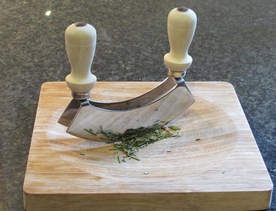 Vorbereitend wird der Romarinzweig abgespült, getrocknet und die die Rosmarinnadeln werden abgestreift. Diese werden zudem mit dem Wiegemesser feingehackt. Außerdem die Knoblauchzehe schälen.