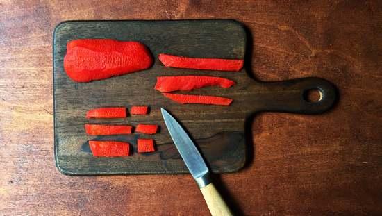 Die rote Paprika waschen und trocken tupfen. Die Paprika halbieren und den Stiel zusammen mit den Kernen  herausbrechen. Die weißen Rippen wegschneiden. Sollten noch einige Kerne verblieben sein, kann man diese durch Klopfen leicht entfernen. Da die Paprika ohne Haut besser verträglich ist, schäle ich sie mit Hilfe des Sparschälers, bevor sie in kleine Sücke geschnitten wird.
