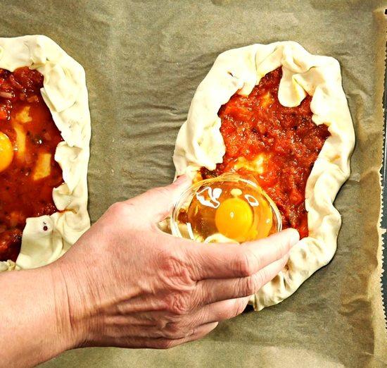 Mit einem Esslöffel eine Mulde in die Füllung machen und jeweils ein Ei in diese geben.