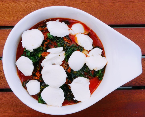 Anschließend die Minikugeln Mozzarella in kleine Scheiben schneiden und diese darüber geben.
