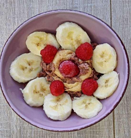 Das fertige Porridge in die Müslischale geben und mit den Bananenscheiben, der Erdnussbutter sowie den Himbeeren garnieren.