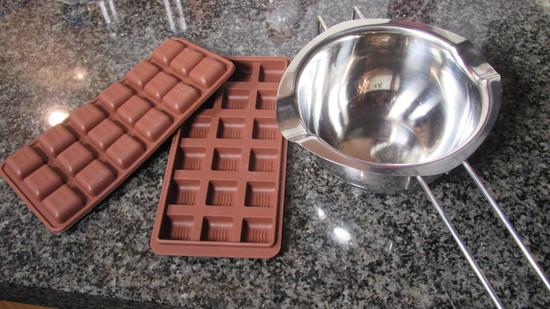 Um die Kuvertüre zu schmelzen, wird zunächst einmal Wasser im Topf erhitzt. Der Topf sollte nur etwa zu 3/4 mit Wasser gefüllt sein, damit die Wasserbad-Schmelzschale nicht im heißen Wasser hängt, sondern tatsächlich nur über dem Wasserdampf. Das Wasser darf jedoch nicht kochen. Sonst würde die Schokolade zu heiß werden und nicht richtig schmelzen, sondern klumpig werden.