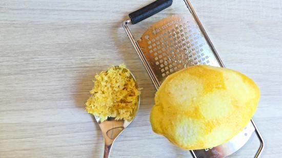 Eine Zitrone gründlich waschen, abtrocknen und mit der Zestenreibe die Zesten von der Zitrone abreiben.