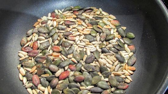 In der Pfanne zunächst die Sonnenblumenkerne und die Kürbiskerne ohne Fett rösten, damit sie ihr Aroma besser entfalten. Wenn sie geröstet sind, die Pfanne vom Herd nehmen und beiseite stellen.
