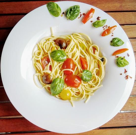 Abschließend die fertigen Spaghetti pomodore e basilico auf Pastatellern anrichten. Wer mag, gibt noch etwas Olivenöl sowie Basilikumblätter darüber.